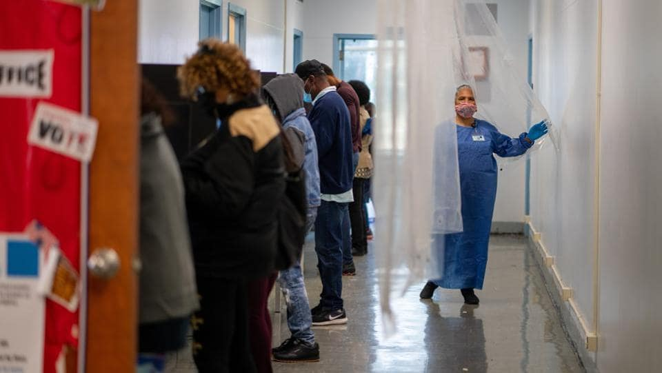 A poll worker walks past people casting their votes in New Orleans, Louisiana on October 16. So far the turnout has been lopsided, with Democrats outvoting Republicans by a 2:1 ratio in the 42 states included in the Associated Press count. Republicans have been bracing themselves for this early Democratic advantage for months, as they've watched President Donald Trump rail against mail-in ballots and raise worries about fraud. (Kathleen Flynn / REUTERS)