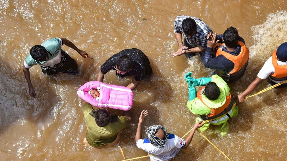 GHMC personnel carry an infant during an operation to move flood-affected people to a safer place, at Hafiz Baba Nagar in Hyderabad.