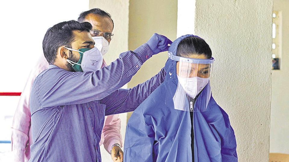 A health worker at a Covid -19 testing centre in Pune straps a face shield on Sunday.