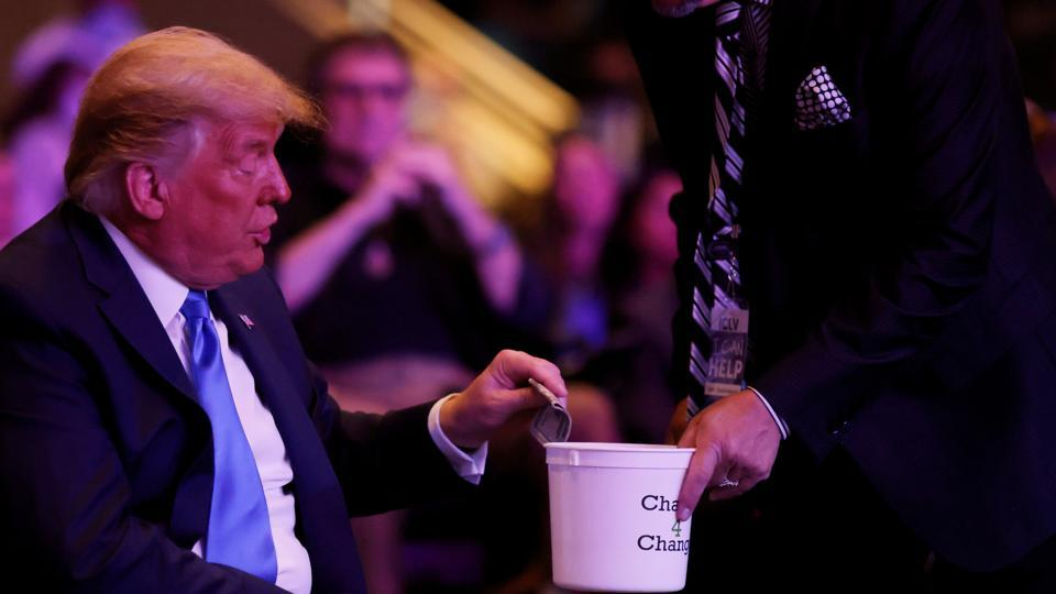 US President Donald Trump donates money as he attends a mass at the International Church of Las Vegas in Las Vegas, Nevada.
