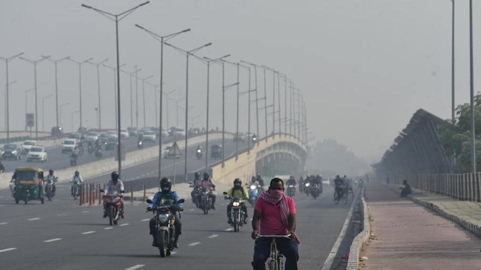 Vehicles move on the road during the smoggy morning as the air quality dips, in New Delhi.