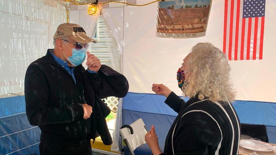 """Holocaust survivors Israel """"Sasha"""" Eisenberg, left, and Ruth Brandspiegel are reunited on Oct. 3, 2020, in East Brunswick, N.J. for the first time in more than 70 years since their families left the Hallein Displaced Persons Camp in Austria. They met under a sukkah, a temporary shelter used to celebrate the weeklong Jewish fall holiday of Sukkot."""