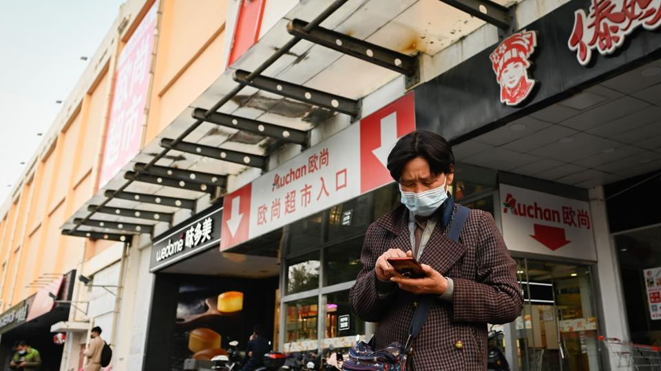 A woman wearing a face mask uses her mobile phone at the entrance of Auchan supermarket in Beijing on October 19, 2020.