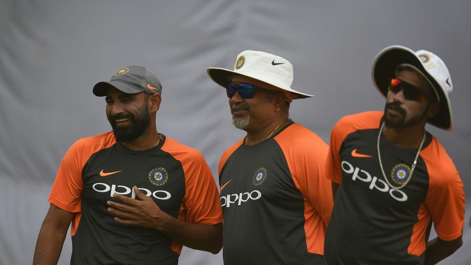 Indian cricketer Mohammed Shami (L) bowling coach Bharat Arun (C) and Mohammed Siraj looks on at nets during a training session.
