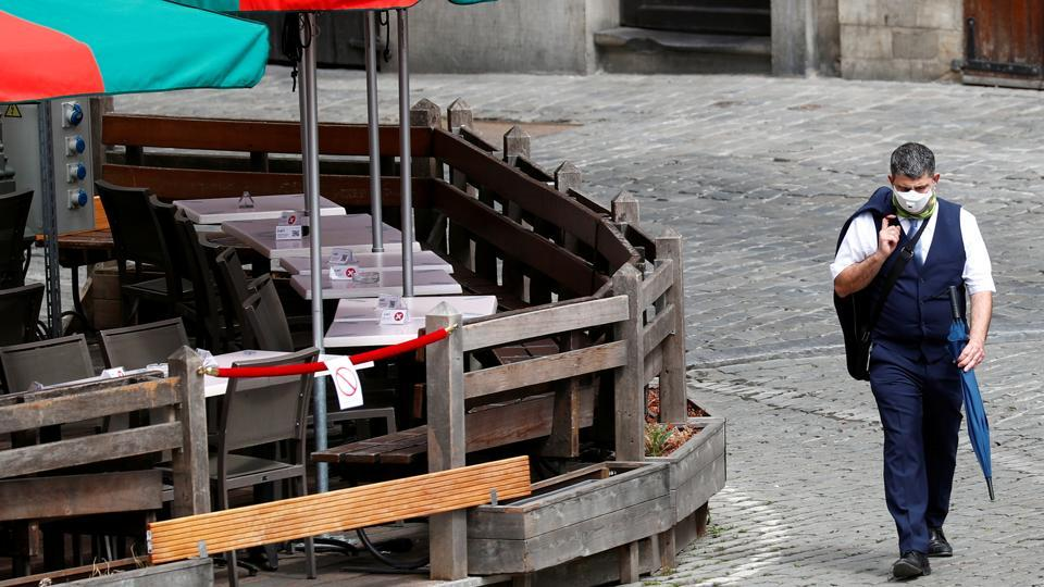 In picture - Man wearing a face mask walks past a terrace on Brussels Grand Place