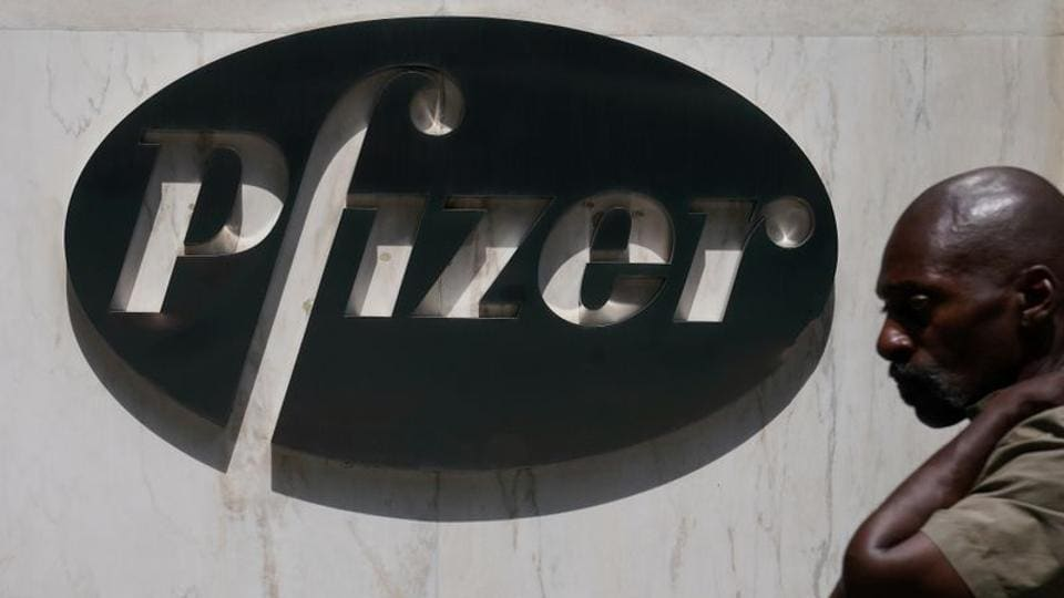 A man walks past a sign outside Pfizer Headquarters in the Manhattan borough of New York City, New York (REUTERS/Carlo Allegri/File Photo)