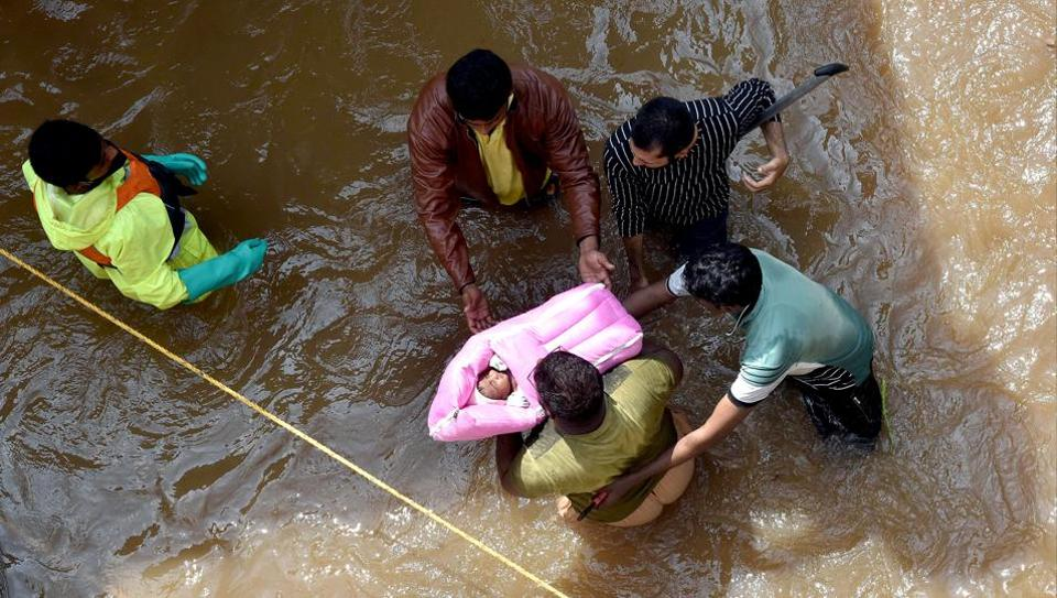 The Greater Hyderabad Municipal Corporation (GHMC) rescuing an infant from flood-affected Hafiz Baba Nagar following heavy rainfall, in Hyderabad on Sunday (ANI Photo)
