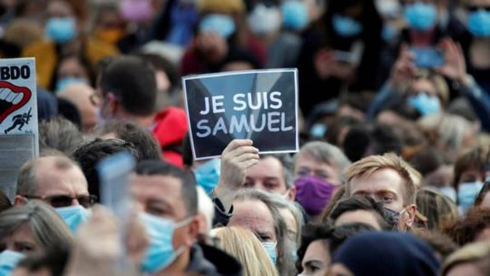 People gather at the Place de la Republique in Paris, to pay tribute to Samuel Paty, the French teacher who was beheaded on the streets of the Paris suburb of Conflans-Sainte-Honorine, France.