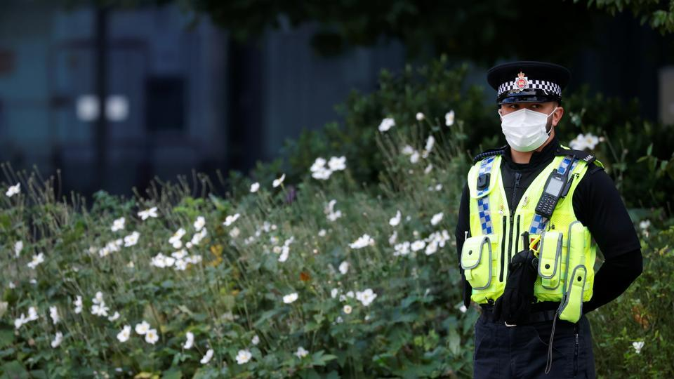 A police officer wearing a protective mask looks on, amid the outbreak of the coronavirus disease, in Manchester, Britain.