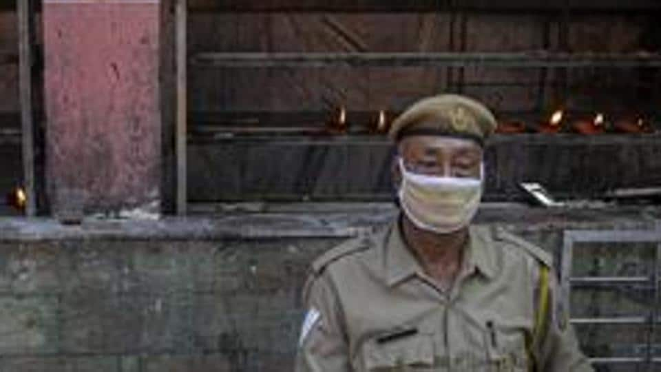 A security person sits wearing mask at the Kamakhya Temple in Assam's Guwahati in this file photo.
