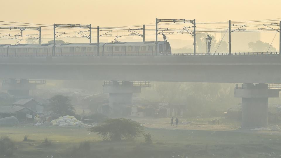 A Metro train runs on a track amid hazy weather conditions, in New Delhi on  Monday.