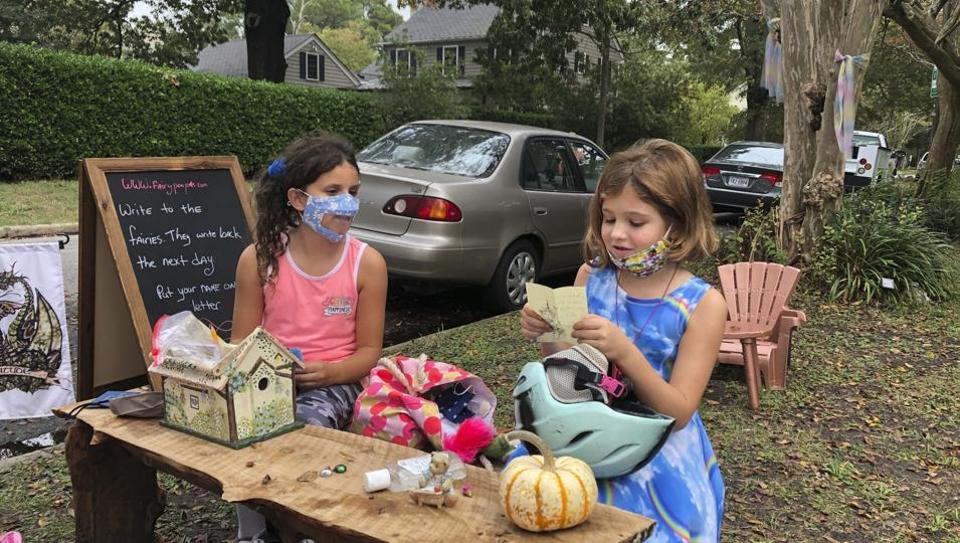 Maya Gebler and Cate Carroll read letters they've received from fairies in Norfolk, Va., on Monday Oct. 12, 2020. In the last few months, more than 700 letters have arrived at a fairy tree village outside the home of a journalist and children's book author.