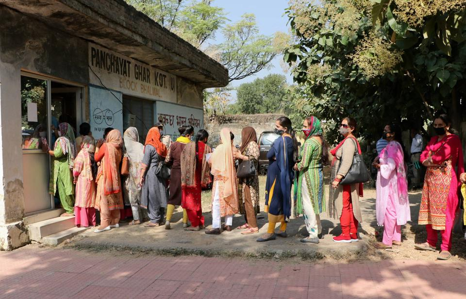 Employees of a government school queue up to register their names for COVID-19 test, on the outskirts of Jammu.