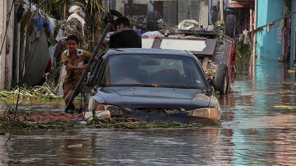 A boy wades through a flooded street after heavy rainfall at Baba Nagar in Hyderabad, on October 18.