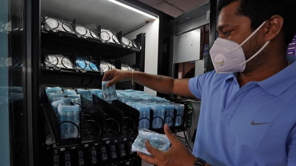A worker wearing a protective face mask fills a vending machine selling protective face masks and gloves at Dadar railway station.