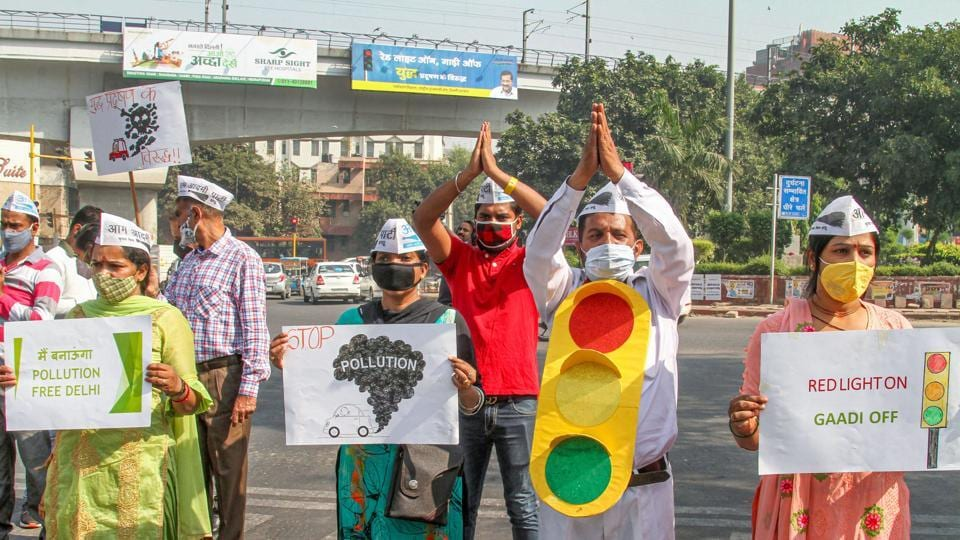 AAP workers hold placards during 'Red Light On, Gaadi Off' campaign to create awareness, near Rajendra Place Metro Station in New Delhi on October 19.