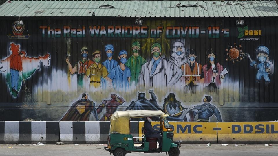 An auto rickshaw drives past a mural depicting frontline workers fighting against Covid-19 in New Delhi.