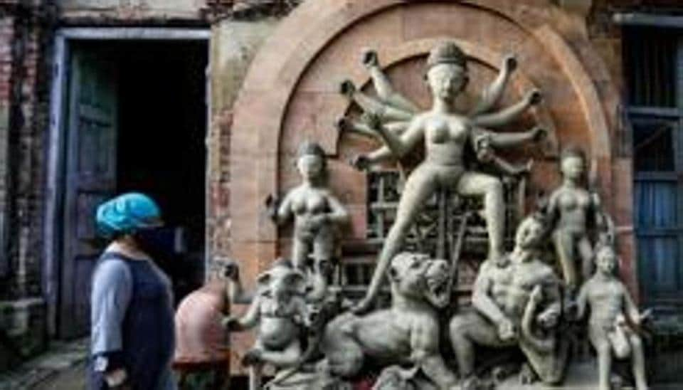 People wearing face masks to prevent the spread of the coronavirus walk past an unfinished clay idol of Hindu goddess Durga ahead of Durga Puja festival in Kolkata.