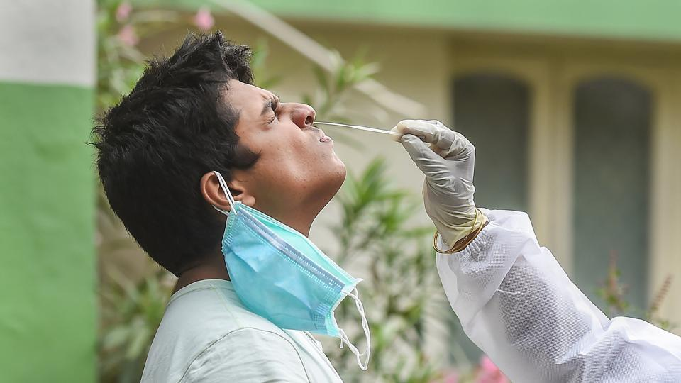 A health worker collects swab sample from a resident for Covid-19 test in Chennai.