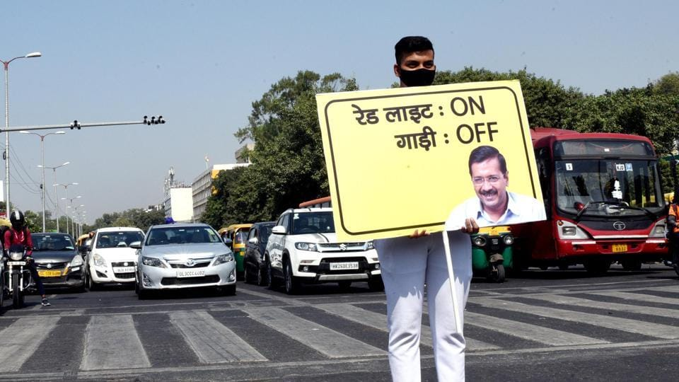 A volunteer holds a placard for 'Red Light On, Gaadi Off'' campaign at ITO crossing in New Delhi, India, on Wednesday, October 21, 2020.