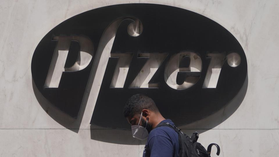 A man walks past a sign outside Pfizer Headquarters in the Manhattan borough of New York City.
