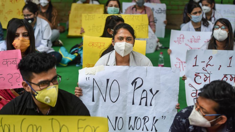 Resident doctors association members of Hindu Rao Hospital hold placards during a protest demanding their outstanding remuneration, at Jantar Mantar in New Delhi on Thursday.