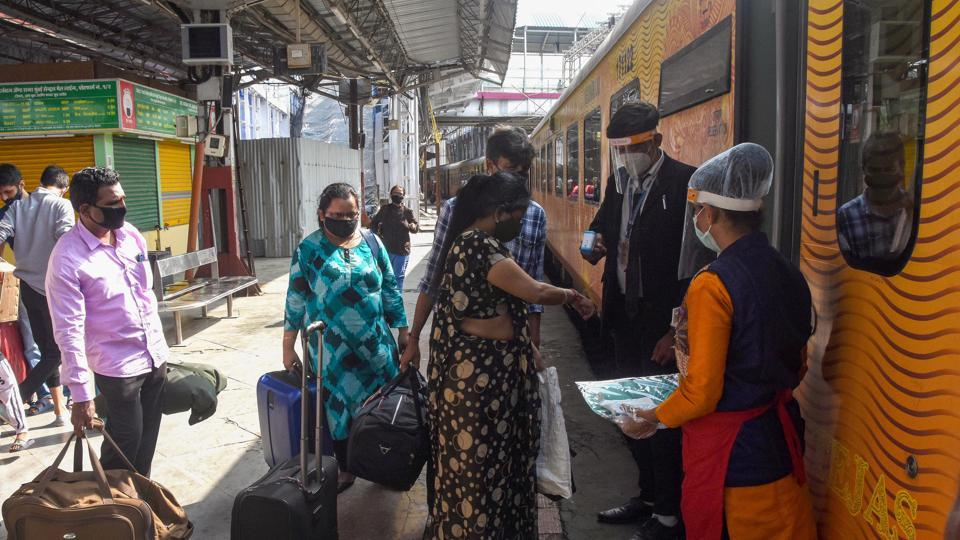 Railway staff members distribute PPE kits to passengers before they board Tejas Express train.