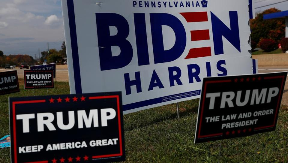 Campaign signs for US Democratic presidential candidate Joe Biden and vice presidential candidate Kamala Harris stand with signs for US president Donald Trump on a hillside in Monroeville, Pennsylvania, US (REUTERS/Shannon Stapleton)