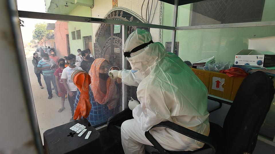 A health worker collects a swab sample from a woman for coronavirus testing at a mobile Covid-19 testing van, at New Ashok Nagar, in New Delhi.
