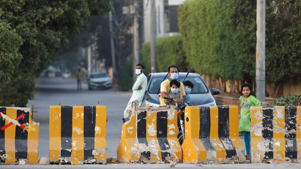 Men and children wear protective masks along a street, blocked by barriers, after Pakistani authorities announced to re-impose lockdowns in selected areas in an effort to stop the spread of the coronavirus disease (Covid-19) in Karachi, Pakistan on June 18, 2020.