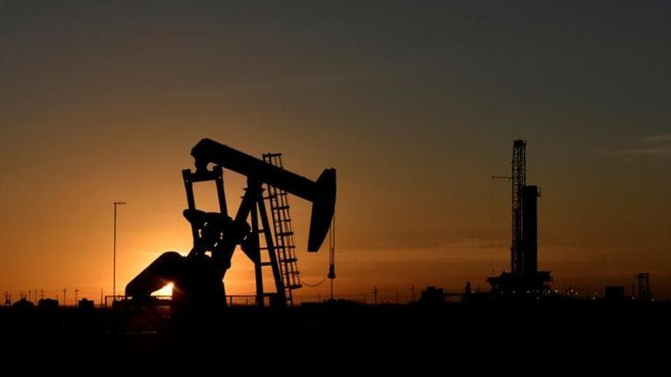 A pump jack operates in front of a drilling rig at sunset in an oil field in Midland, Texas US.