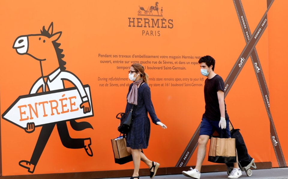 Residents, wearing protectice face masks, walk past a Hermes store in Paris, France.