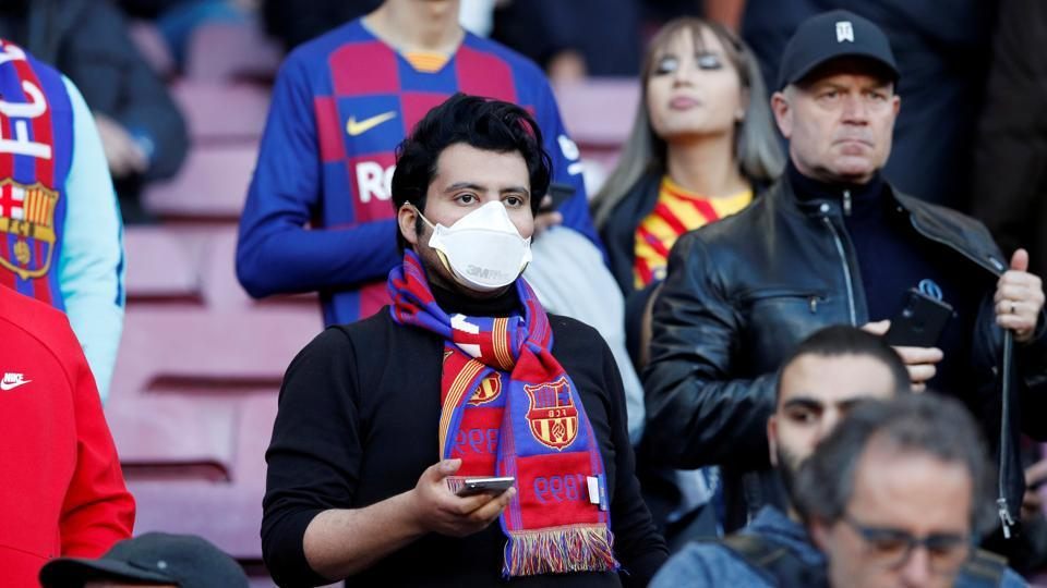 Soccer Football - La Liga Santander - FC Barcelona v Real Sociedad - Camp Nou, Barcelona, Spain - March 7, 2020 A Barcelona fan wears a mask before the match due to the recent coronavirus outbreak REUTERS/Albert Gea/File Photo