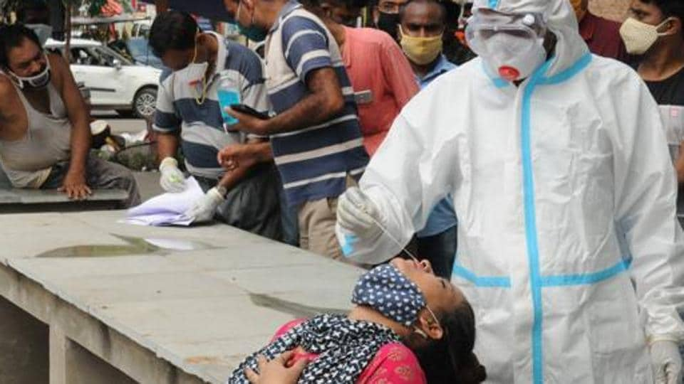 Health worker in PPE kit collects swab sample at the market at Boring road for Covid 19 test, in Patna, Bihar.