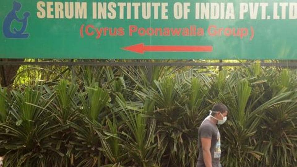 A man walks past a signpost of Serum Institute of India, the world's largest maker of vaccines, which is developing a vaccine against the coronavirus disease (Covid-19) at its laboratory in Pune.
