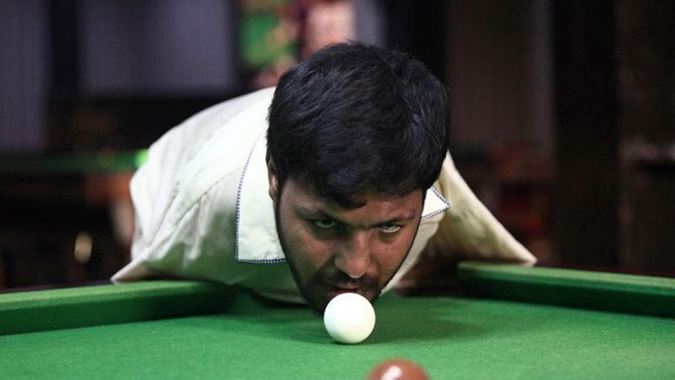 Muhammad Ikram, 32, who was born without arms, plays snooker with his chin at a local club.