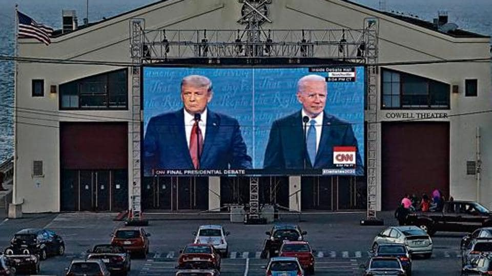 People watch the final presidential debate between Donald Trump and Joe Biden on a giant screen from their vehicles at Fort Mason Center in San Francisco, US.