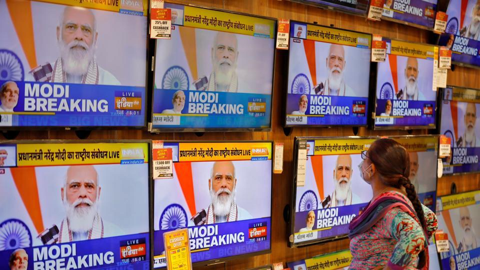 A woman wearing a protective mask watches Indian Prime Minister Narendra Modi on TV screens inside a showroom, amidst the spread of the coronavirus disease in Ahmedabad.