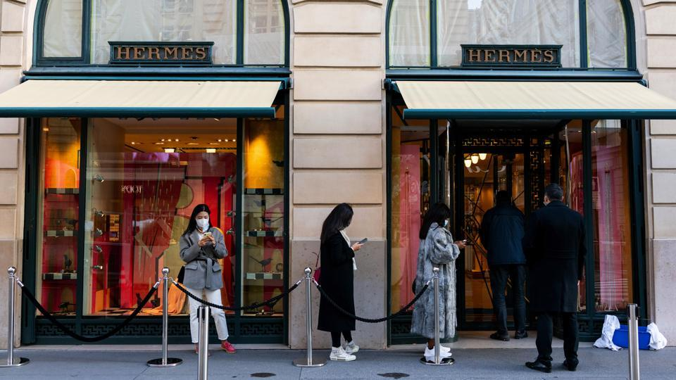 Shoppers form a socially distanced queue to enter a Hermes International luxury good boutique in Paris, France, on Wednesday, Oct. 21, 2020. Hermes report third quarter earnings on Oct. 22.