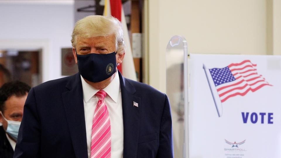 US President Donald Trump wearing a face mask leaves after voting in the 2020 presidential election at the Palm Beach County Library in West Palm Beach, US on October 24, 2020.
