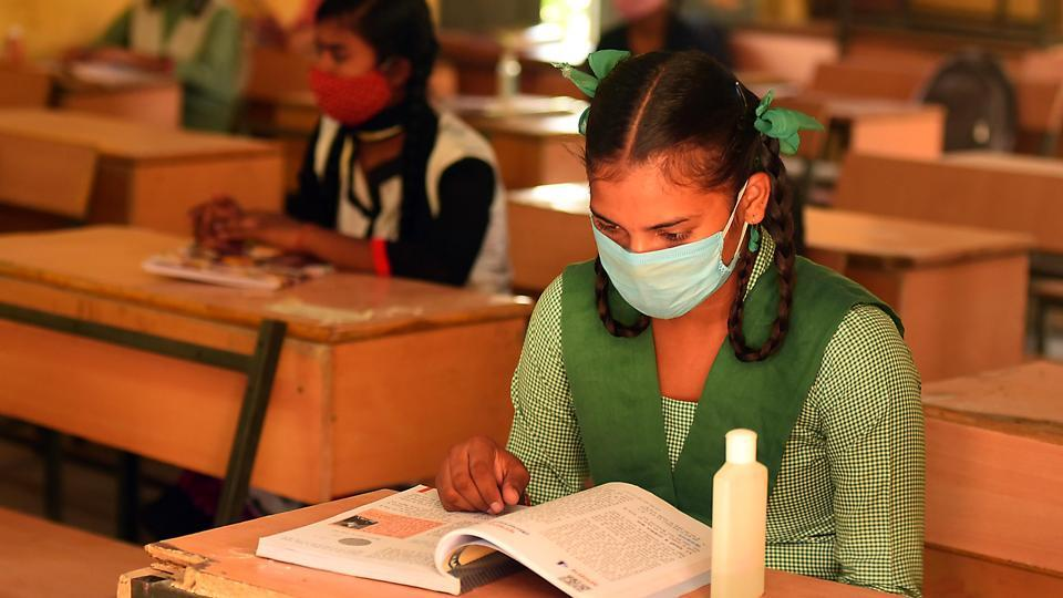 Students wearing face masks as they attend a class after schools partially reopened in a few states amid the coronavirus pandemic.