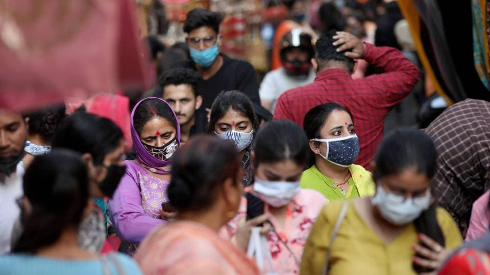 Women wearing face masks as a precautionary measure against the coronavirus visit the crowded Patel Bazar bangles market, in Jammu, on Friday.
