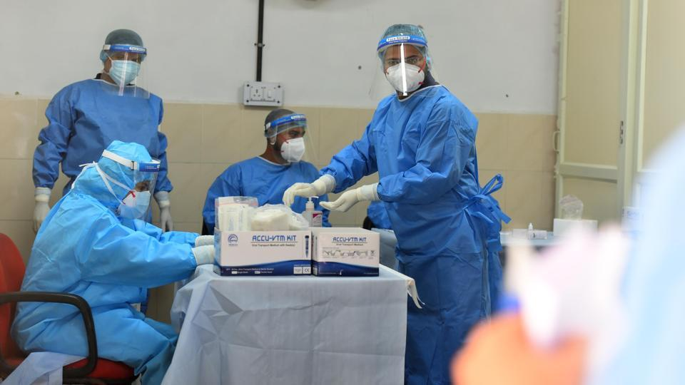 Health workers in PPE coveralls pictured during coronavirus testing.