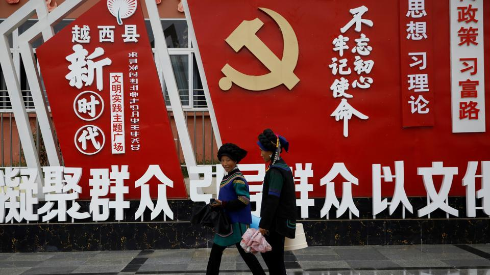 Ethnic Yi women walk past an installation featuring a logo of Communist Party of China at the Chengbei Ganen Community.