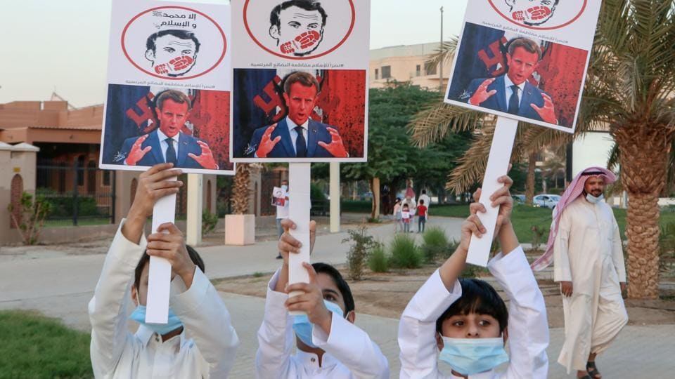 In picture - Kuwaiti youths lift placards expressing anger at French President Emmanuel Macron at a rally in front of the country's National Assembly (parliament) in Kuwait City.