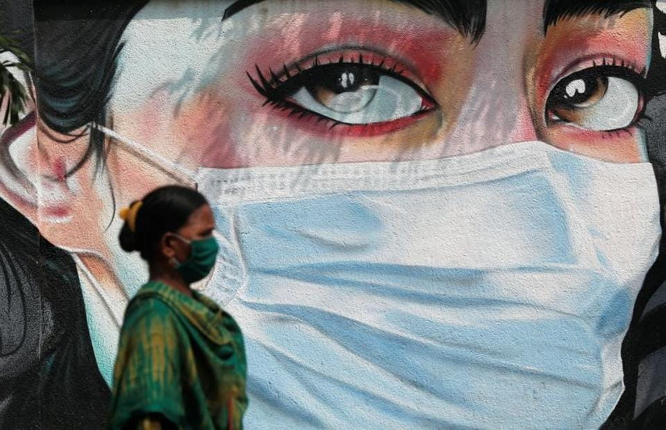 A woman walks past a graffiti of a girl wearing a protective mask amidst the spread of the coronavirus disease in Mumbai, India.