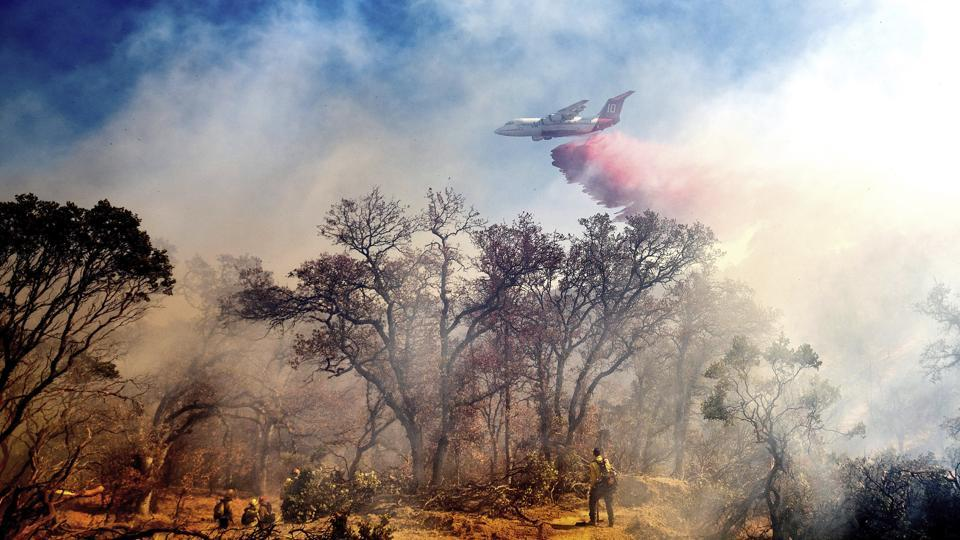 An air tanker drops retardant on the Olinda Fire burning in Anderson, California on Sunday.