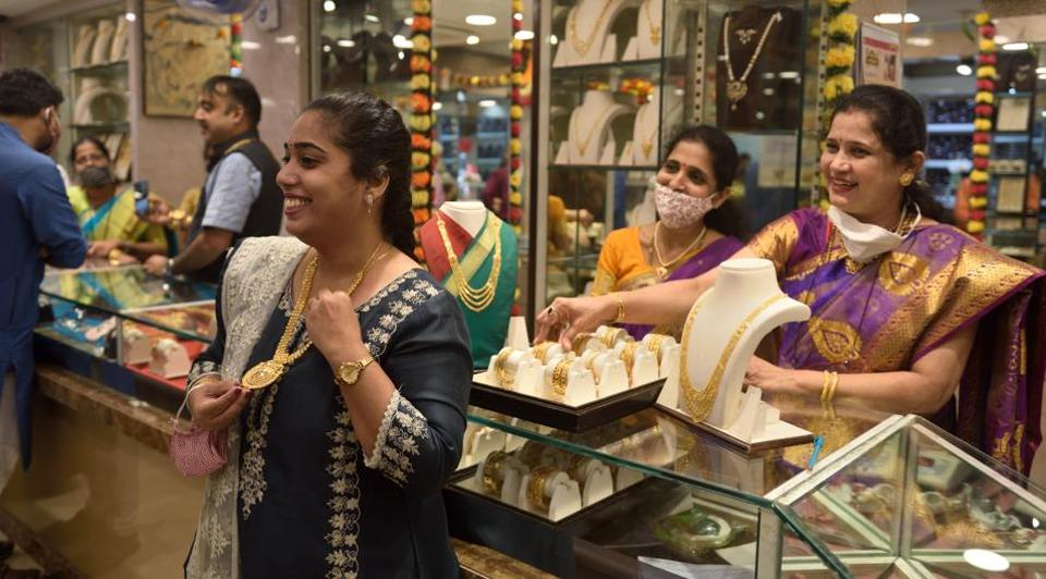 A woman checks out a gold necklace at a jewellery store in Mumbai on Dussehra  on Sunday.
