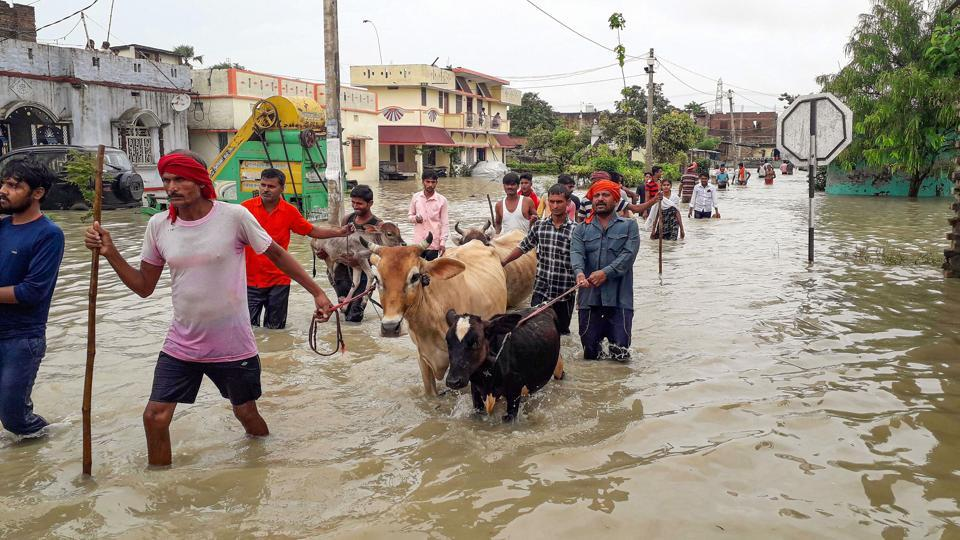 People wade through floodwater as they move to a safer place, Gopalganj, July 24, 2020