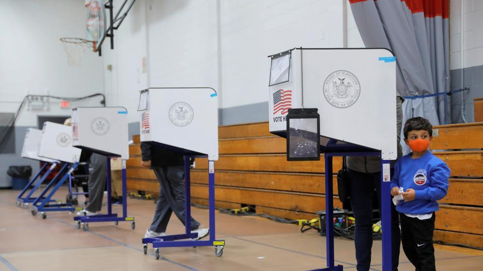 A child waits by a privacy booth as a ballot is filled at a polling station located in the Monsignor John D. Burke Memorial Gym at the Church of the Holy Child in Staten Island during early voting in New York City, US on October 25, 2020.